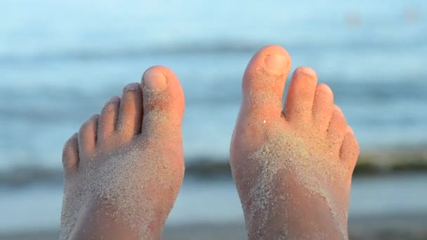Two feet strewn with sand in front of waves of sea in light of sunset sunrise