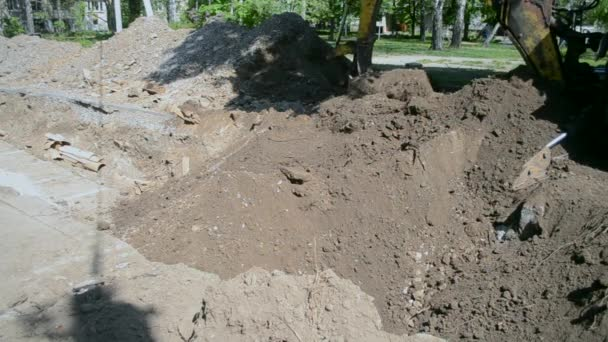 Backhoe piles up the ground close-up.