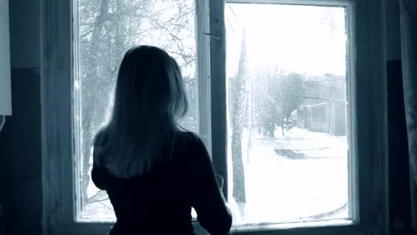 Žena otevře okno doma v zimě.