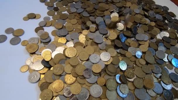 Person nimmt eine Handvoll Münzen in die Hand und wirft sie über Münzen auf den Tisch.
