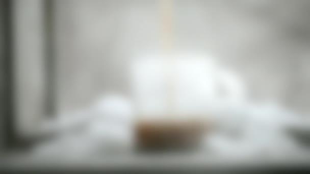 Homályos háttér. Az ember forró kávét tölt tejjel egy üvegbögrébe.