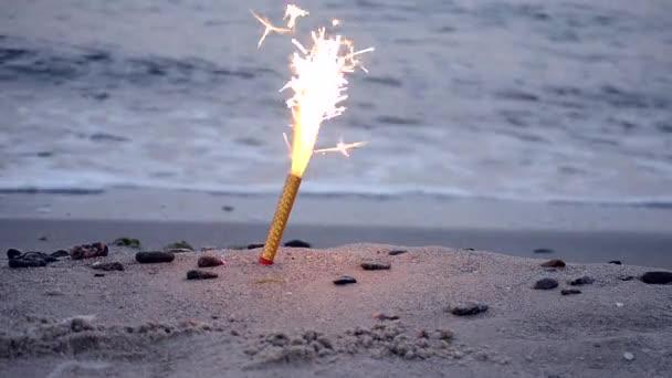 Cake fountain candle with sparks burning on sand on sandy beach on sea ocean