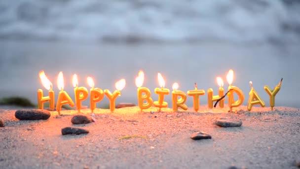 Candles word happy birthday burning on sand on sandy beach