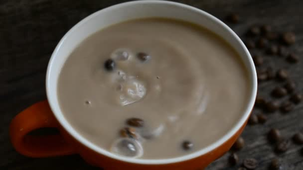 coffee beans fall into a cup of coffee with milk