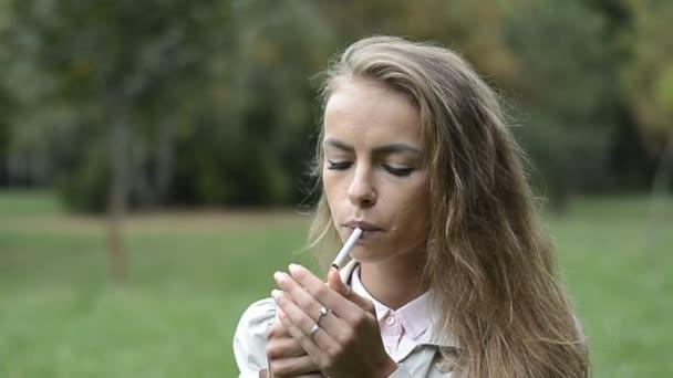 Soziale Probleme: Porträt einer jungen Frau beim Zigarettenrauchen im Stadtpark