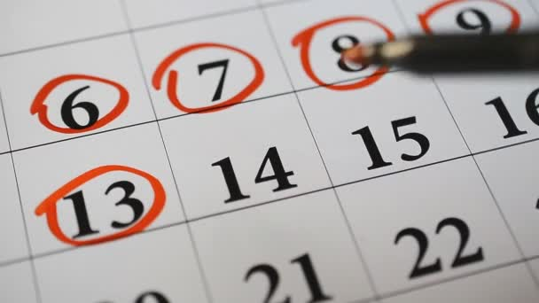 Signing a day on a calendar by red marker