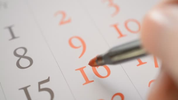 Signing a day on a calendar by red pen