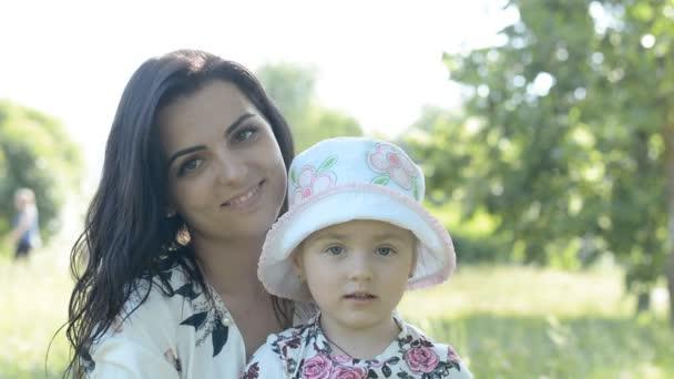 anya és lánya nézi a kamerát a parkban, egy szép nyári napon