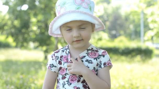 schönes kleines Mädchen blickt an einem sonnigen Sommertag im Park in die Kamera