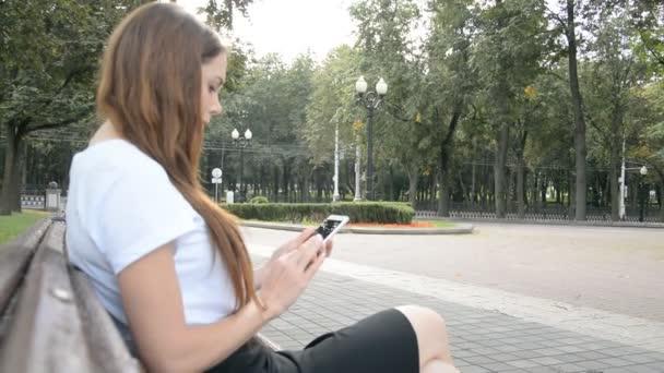 Vážné mladá žena čtení sms na mobil