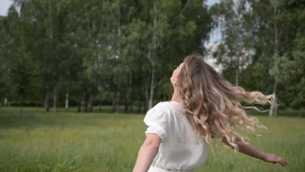 šťastná dívka spinning na trávníku v letním parku