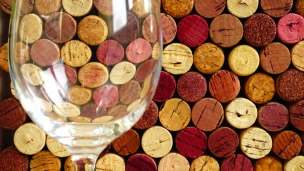 Pouring wine into a glass against the background of wine corks.
