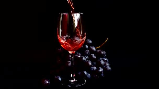Nalít víno do sklenice na černém pozadí. Zpomalený pohyb.