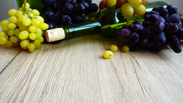 Falling grape berries on a wooden board against the background of a wine bottle and grapes. Slow motion.