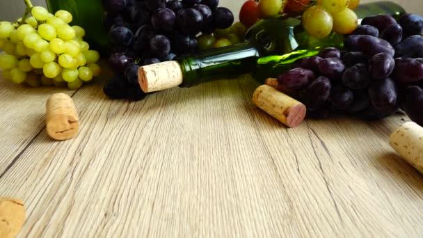 Padající zátky na dřevěnou desku na pozadí vinné láhve a hroznů. Zpomalený pohyb.