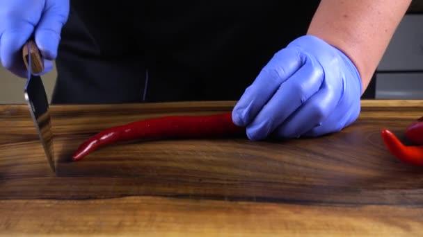 Kuchař krájí chilli papričky na řezací desce.