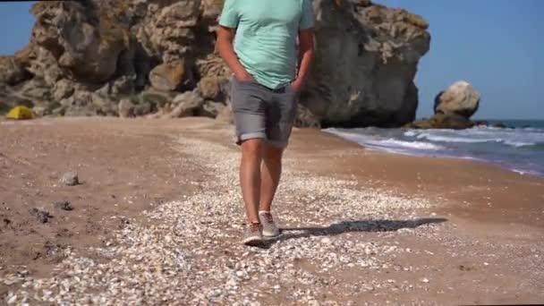 Die Beine eines Mannes in Jeanshosen gehen am Strand in die Kamera, Turnschuhe treten mit Muscheln in den Sand