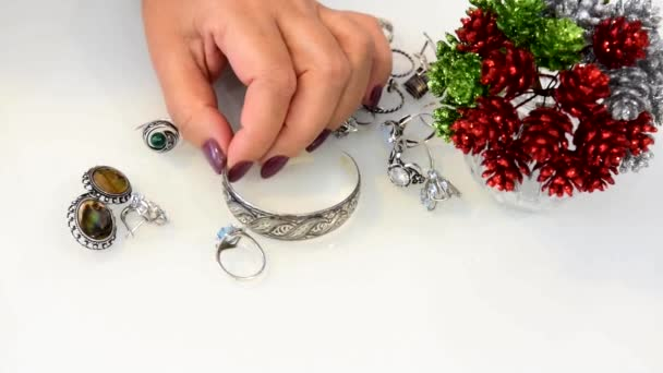 different jewelry on the white table, woman touches jewelry