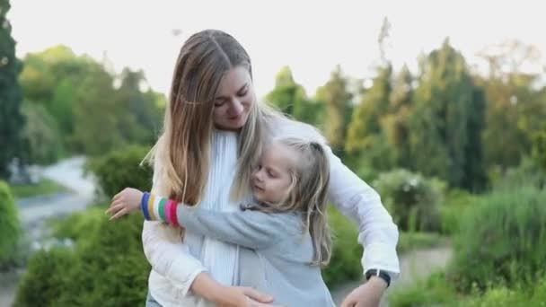 Young happy blond mother and daughter enjoying in the park. Sunset. Slow Motion.
