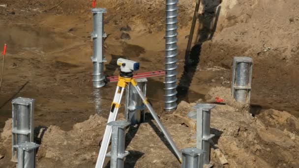 Stavební úroveň a šroub piloty v zemi. rekonstrukce suterénu pod vedení