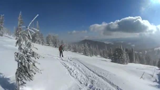 Lyžař a snowboardista na zasněžené sjezdovky na slunný zimní den.
