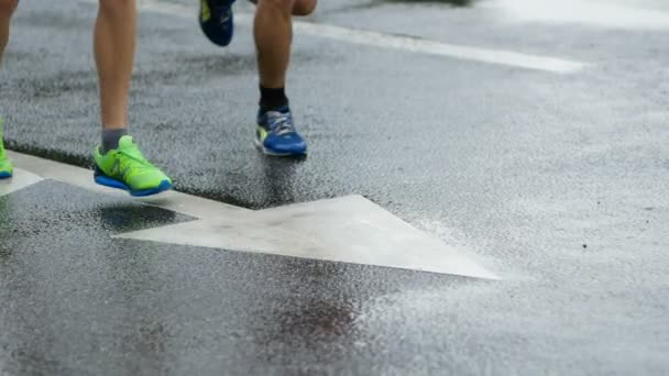 athletes feet on road markings. runners during marathon while it is raining