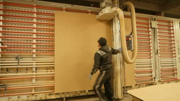 průmyslové tesař pracovník působící dřevo řezací stroj během výroby nábytku dřevěné dveře