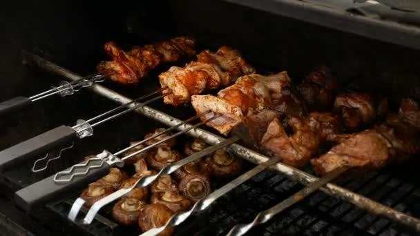 Chutné pečení horký vepřový šašlik na kovové špízy se žampiony níže. BBQ party.