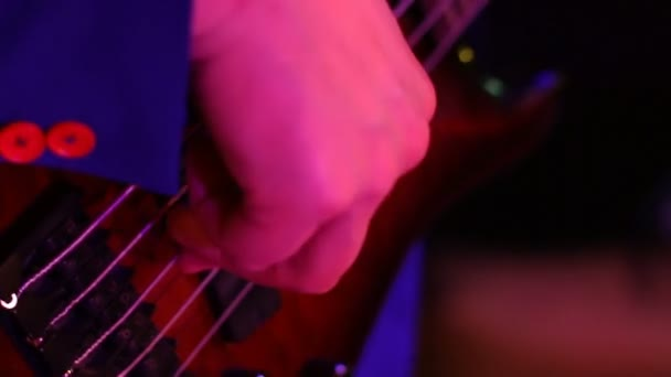 musician plays bass guitar in discolights. hands on the fingerboard