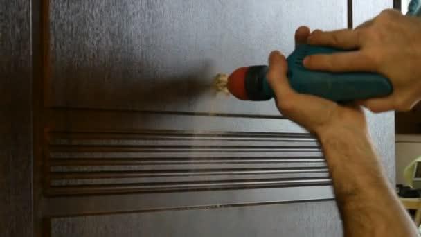Rukou truhlář s elektrickou vrtačku, nudné kukátkem, detail.
