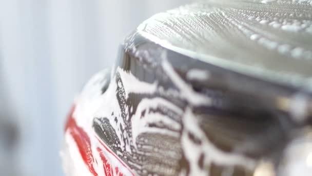 Zpomalený pohyb mužské ruky s pěnová houba mycí Auto světlometů
