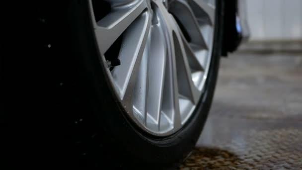 mužské pracovní ruka s látkou ubrousky kapky vody z disku kola po umytí auta
