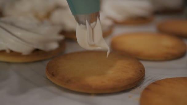 Zblízka se přípravy marshmallow. šéfkuchař s cukrářský sáček ždímá smetanu do souboru cookie na pergamenu v kuchyni shop