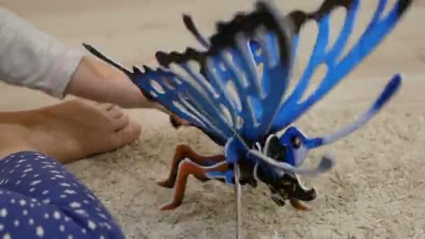 Dívka si hraje s 3d puzzle motýl