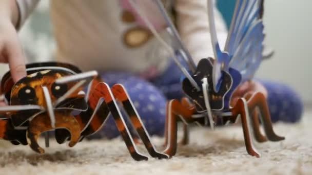 Dívka si hraje s 3d puzzle motýl a mravenec