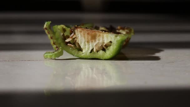 Zöld hernyó kártevő eszik paprika fehér háttér reflexióval. Noctuidae, közismert nevén bagolylepke