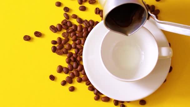 Pro přípravu kávy se do skleněného šálku nalévá horké espreso. Pohled na ruku s šálkem černé kafe na kávu, pozadí.