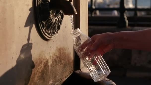 Female hand puts a transparent bottle under a stream of water in the sun in a park