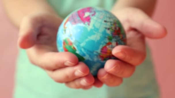 Save the planet concept. Global warming and plastic emissions. Female hand holds planet earth ball
