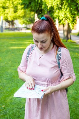 A red-haired girl and in a pink dress holds a map and explores the travel route around the city on a green grass in the park.