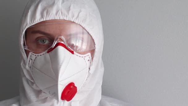 Portrait of a medical officer in a medical mask, glasses and protective white workwear suit for protection against coronavirus, disease, infection, quarantine, medical mask
