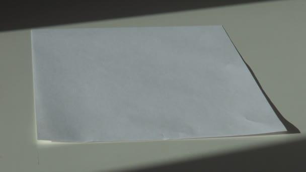 ručně odstraní list bílého papíru z tabulky