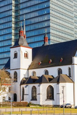Cologne, Germany - July 03, 2017: Alt St. Heribert in Cologne-Deutz in front of an office tower. The church was founded 1003 on the site of a Roman fort by future Saint Heribert, Archbishop of Cologne