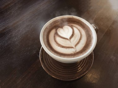 love hot coffee with smoke by latte art on a cup