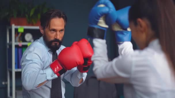 Business people vie boxing on gloves. A man and a woman in business clothes are trying hard to determine which one is stronger. Gender Conflict Concept. Prores 422