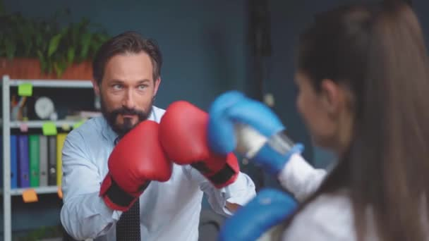 Businesswoman boxing wearing gloves. Man and woman in business clothes are trying to work on stress in work. Gender Conflict Concept. Selective focus on man. Prores 422