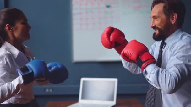 Business people boxing fighting wearing gloves. Man and a woman in business clothes are trying hard to release stressful situations making funny fight. Gender Conflict Concept. Prores 422