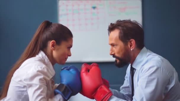 Man frightening woman in business clothes trying hard to determine which one is stronger. Business people vie boxing on gloves. Gender Conflict Concept. Prores 422