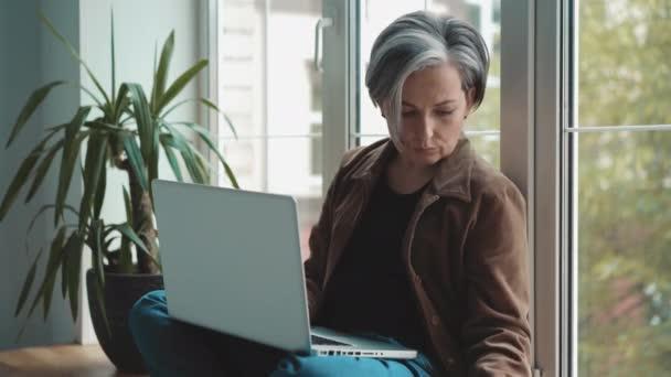 Šedovlasá zralá žena zvedala telefon, zatímco pracovala na laptopu, který se opíral o okno. zralí lidé v podnikání. Obchodní koncept. Prores 422