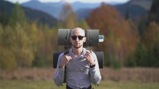 Bold handsome tourist guy in sunglasses gesture OK smiling on camera standing straight. Hiker with a large backpack in the Carpathian Mountains. Slow motion. Prores 422